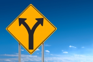 An informational traffic sign over a blue sky showing a division of directions - a clipping path is included to separate sign from bkg.